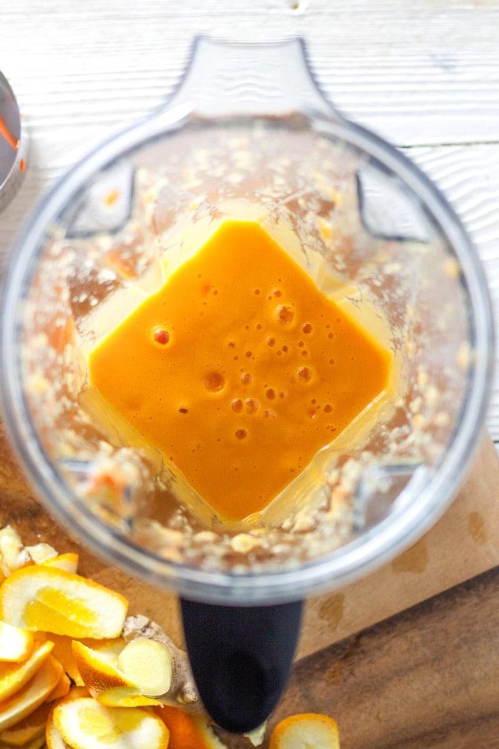 Blender full of carrot and orange juice.