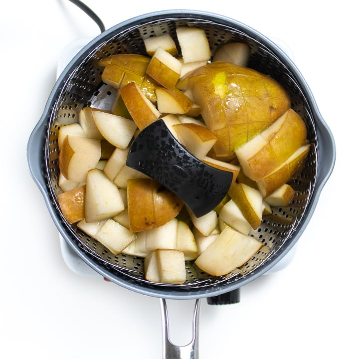 Steamer basket with cooked pears for baby puree.