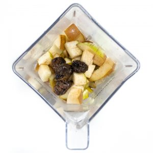Blender with steamed pears, prunes and cloves ready to pureed.