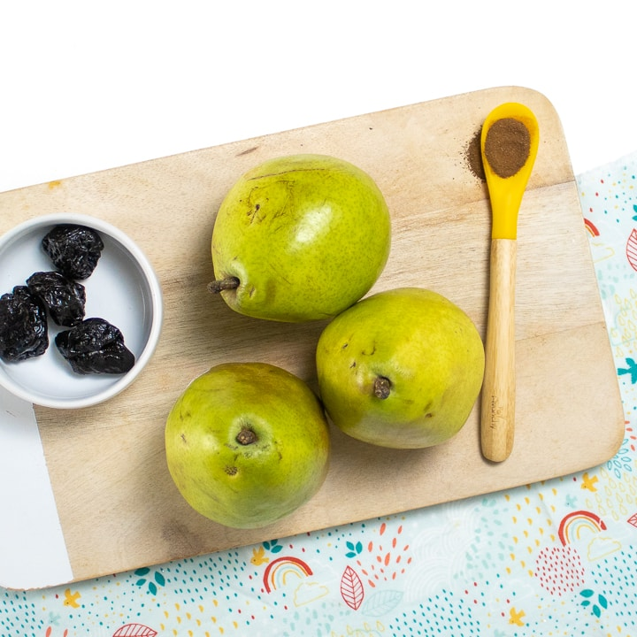Cutting board with pears, dried prunes and cloves.