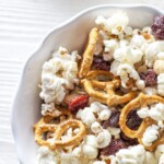 A bowl of popcorn with trail mix inside.