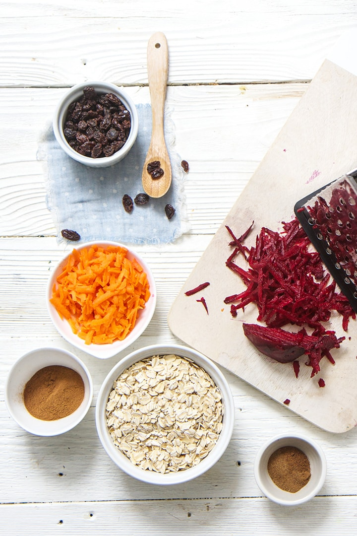 Spread of beets, carrots, oats, raisins and spices on a white board.