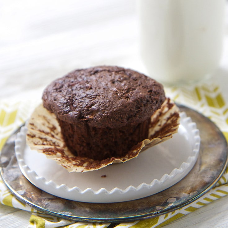 A chocolate pear whole wheat muffin on a white plate.
