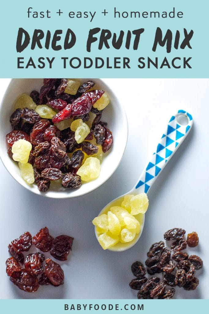 A bowl of dried fruit mix with a toddler spoon on a white background.