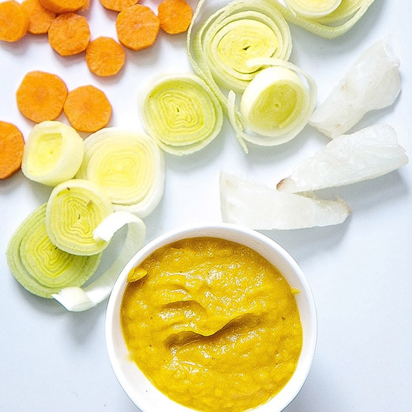 White cutting board with a spread of carrots, leeks and fish and a small bowl of baby food puree.
