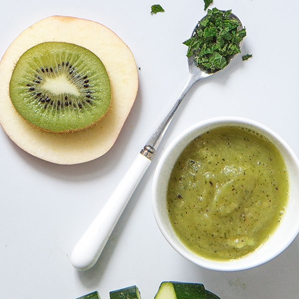 White cutting board with a spread of ingredients for this baby food puree - zucchini, apple, kiwi, mint and a bowl filled of the puree.
