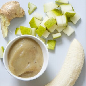 A bowl of banana and pear puree surrounded by bananas, pears, and fresh ginger.