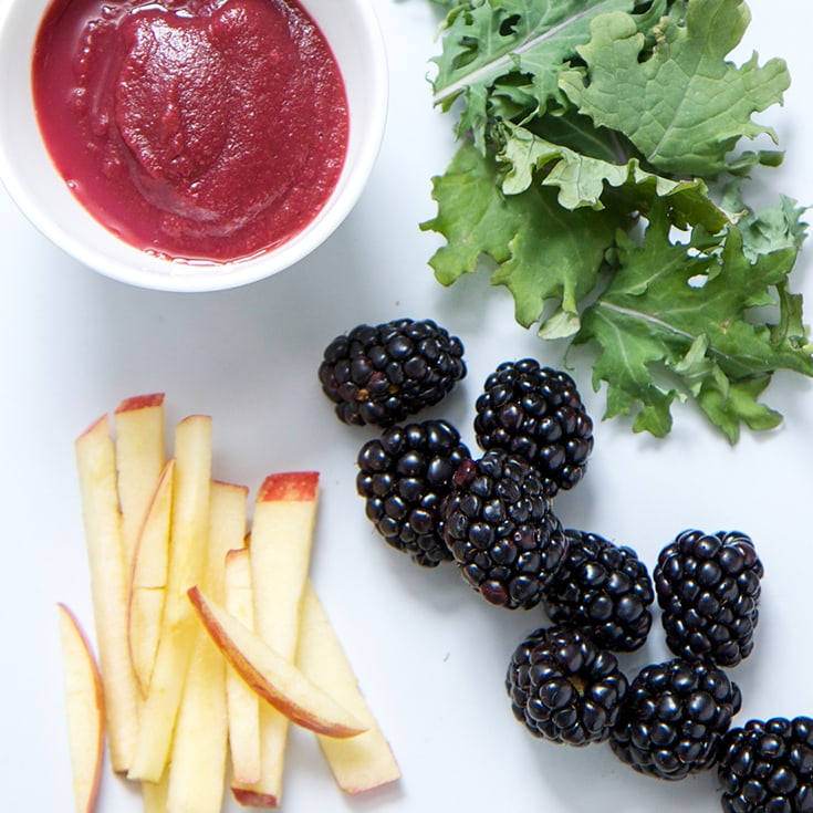 A bowl of fruit kale puree surrounded by blackberries, apples, and kale leaves.