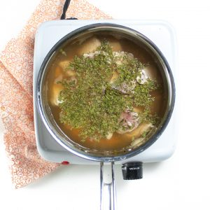 Saucepan full of broth, chicken and parsley.