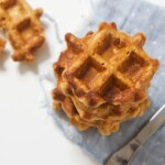 An overhead shot of a stack of sweet potato waffles with one waffle on the white background half eaten - stack of waffles is on a blue napkin