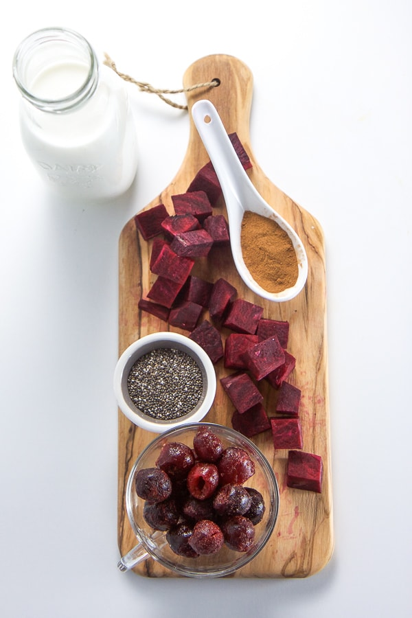 Ingredients for a cherry beet smoothie arranged on a white background.