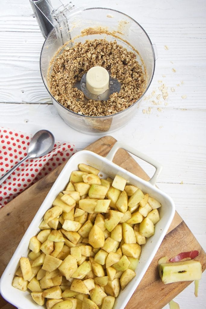 baking dish with apples and a the topping ready to sprinkle on top against a white background.
