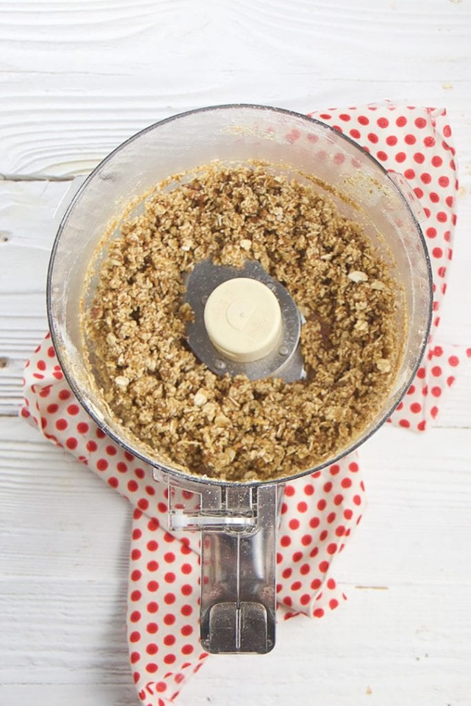 food processor is filled with apple crispy topping.
