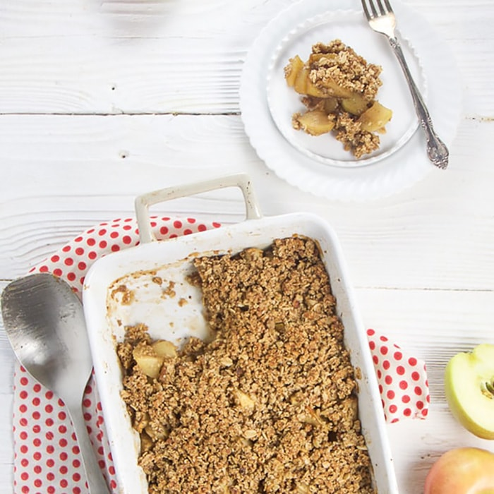 Baked apple crisp is cup with a serving on a plate.