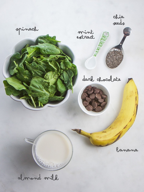 Ingredients for a mint chocolate smoothie arranged on a white background.