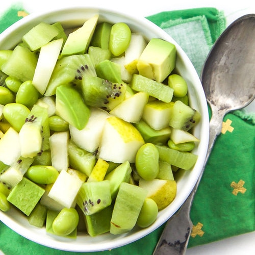 A baby led weaning finger salad in a white bowl with pear, avocado, kiwi, and edamame.