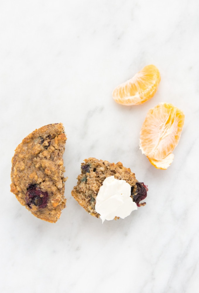 Blueberry oatmeal muffins with orange slices on marble counter