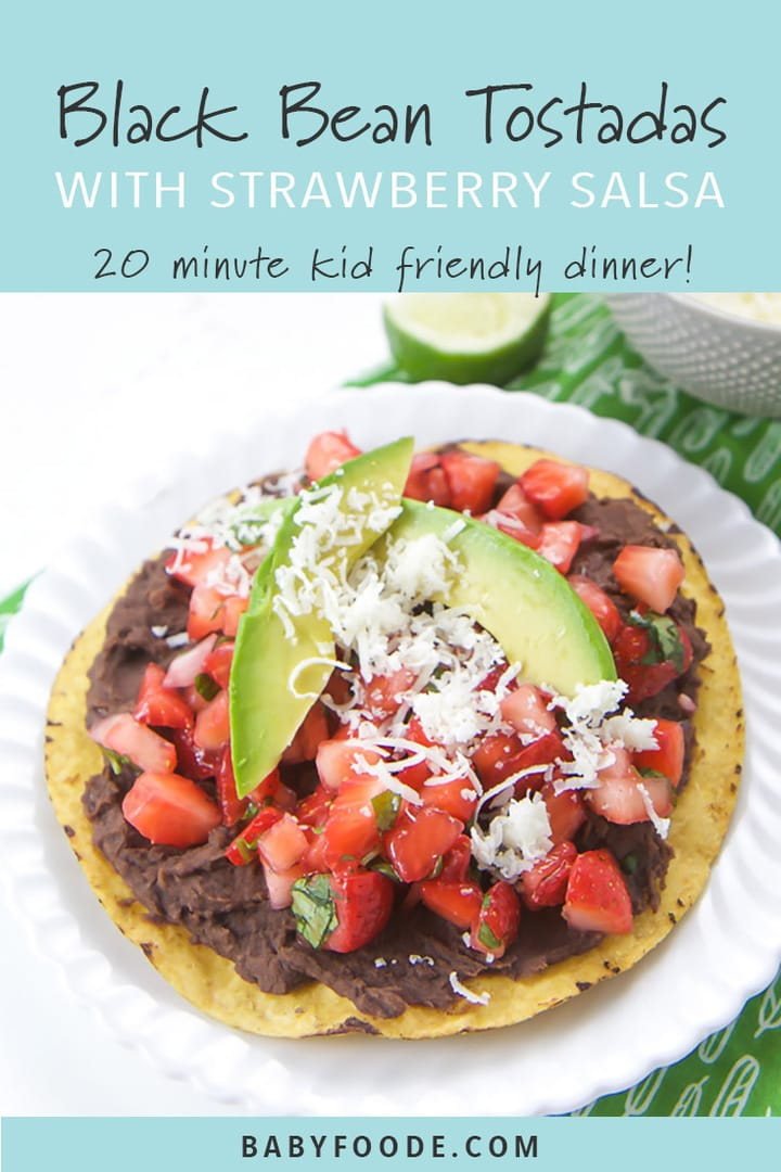A black bean tostadas topped with strawberry salsa and a avocado on a white plate.