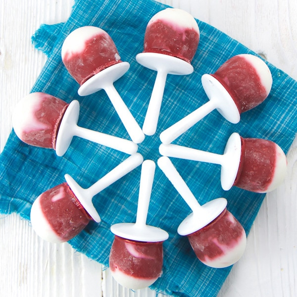 Hidden veggie beet popsicles in a circle on a blue napkin.