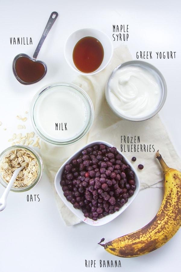 Oats, banana, blueberries, milk, yogurt, vanilla, and maple syrup flat lay