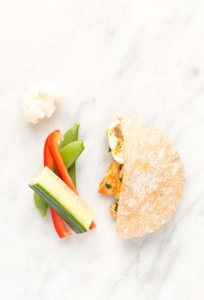 Pita, cucumber, red pepper, and peas on marble counter top