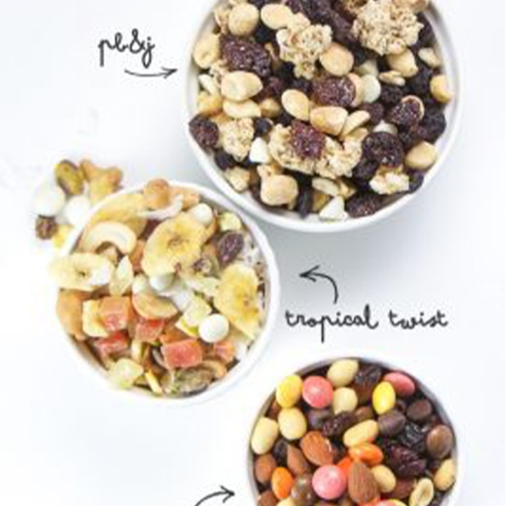 Three trail mixes in white bowls.