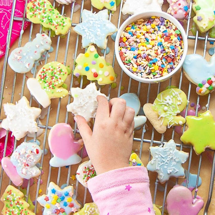 Small kids hands reaching for a sugar cookie.