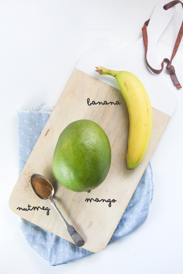 mango baby food recipe - picture of a cutting board sitting on top of a blue napkin with a banana, mango and nutmeg on top