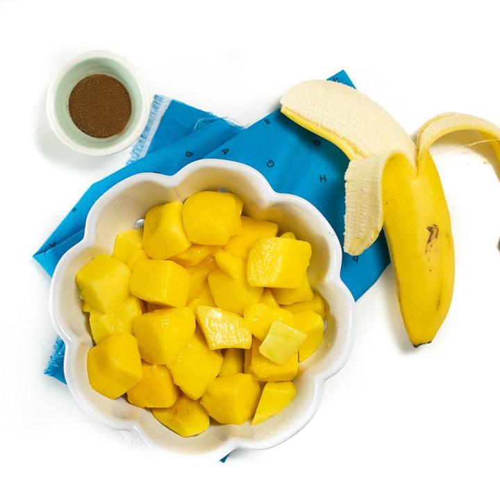 Spread of ingredients for mango baby food puree - mango, banana, nutmeg.