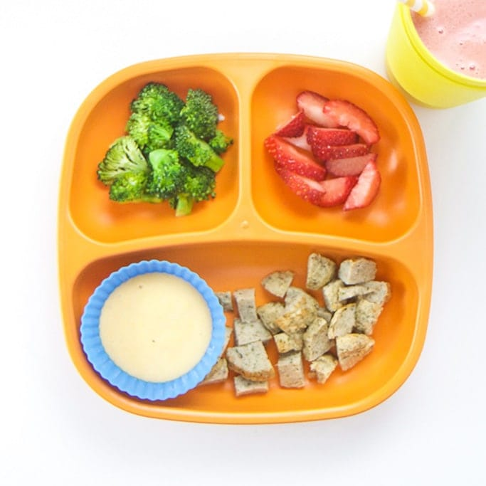 A nutritious lunch for toddlers on a sectioned orange plate.