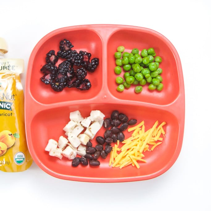 A 3-section red plate sitting on a white surface, plate is filled with finger foods for toddlers and on the side is a fruit and veggie pouch.