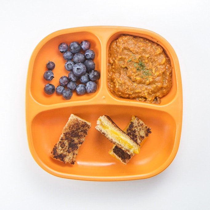 a 3-section plate on a white surface filled with grilled cheese dippers, soup and blueberries.