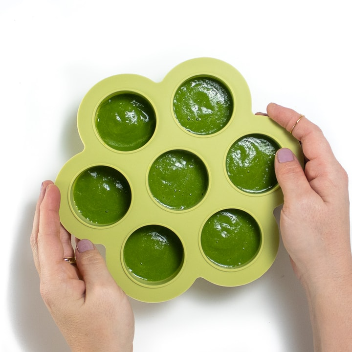 Hands holding a freezer container filled with green bean baby food.