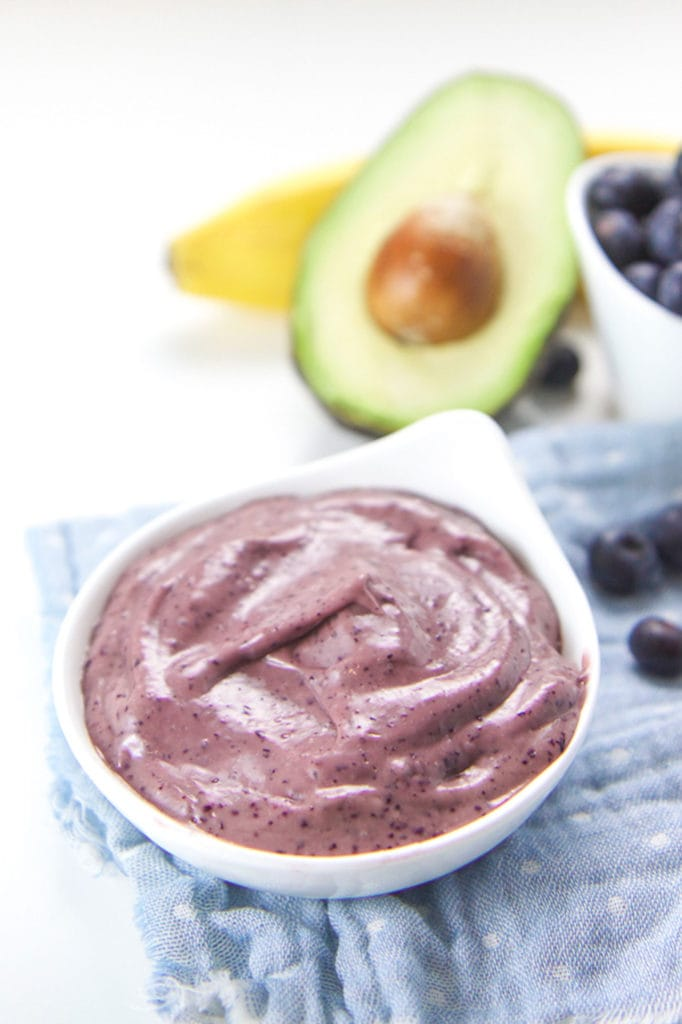Small white bowl filled with blueberry banana avocado baby food puree.