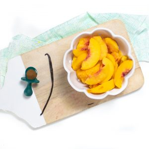 Cutting board with peaches, vanilla bean and cloves.
