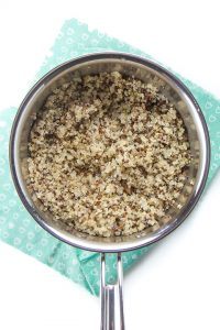 Silver saucepan filled with cooked quinoa.