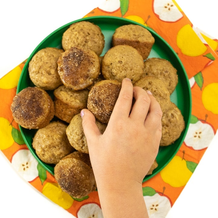 Green plate with small toddler hand reaching for a mini muffin.