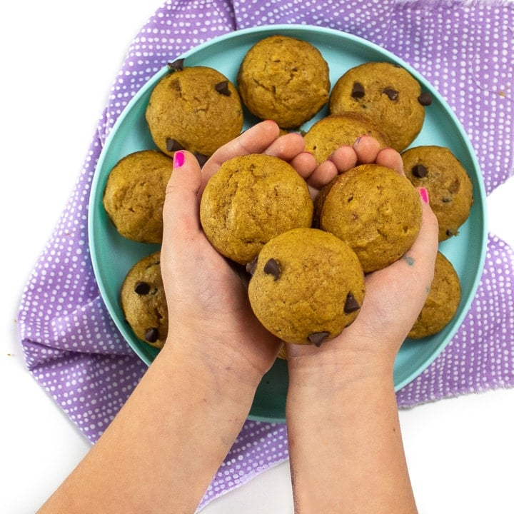 Small hands holding mini muffins in front of a teal plate with more muffins.