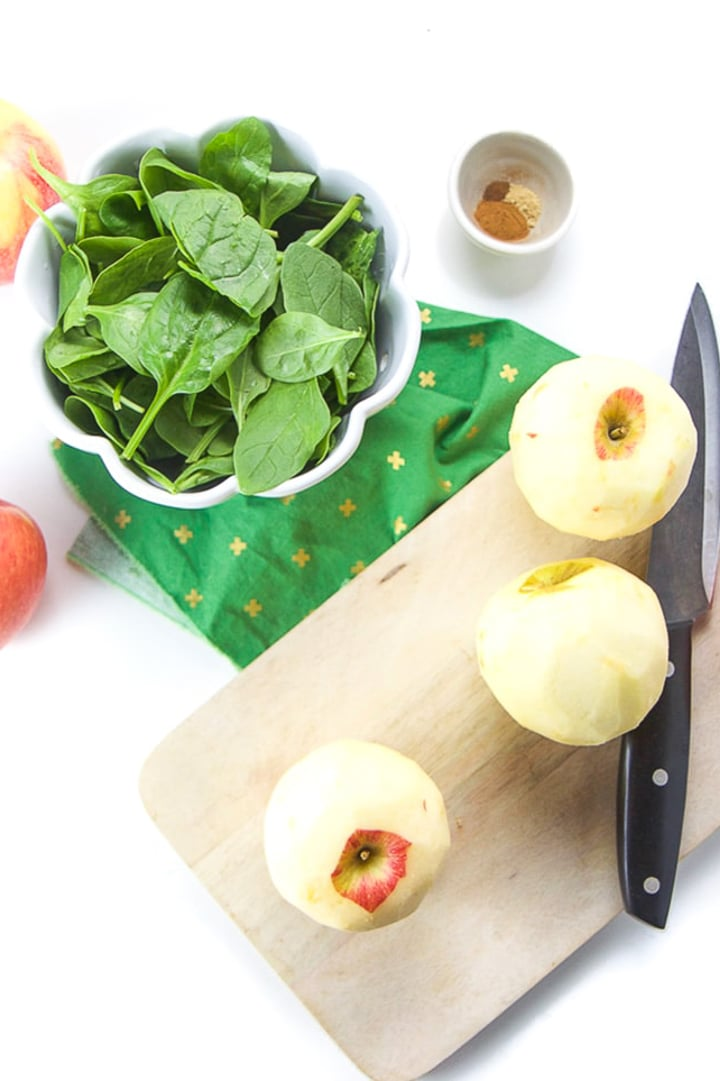 Cutting board with peeled apples on it with bowl of spinach next to it.
