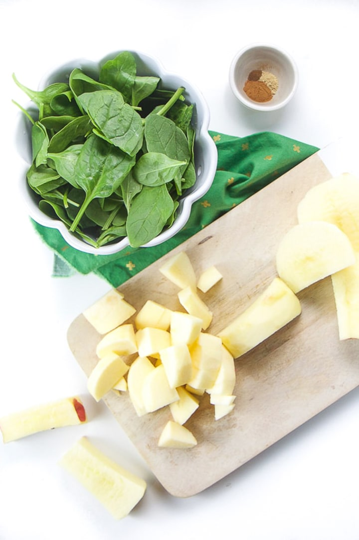 Cutting board with chopped apples and a white bowl of spinach sitting next to it.