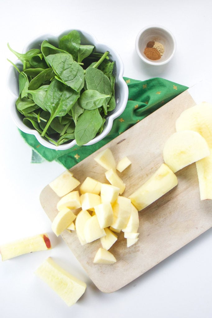 chopped apples with a side bowl of spinach and another small bowl of spices.