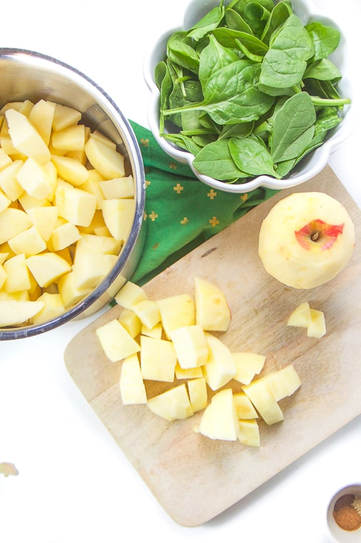 Cutting board with chopped apples with a saucepan next to it with more chunks of apple in it.