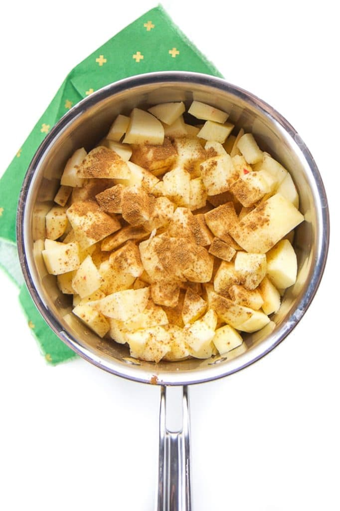 Apples in a saucepan with cinnamon on top.