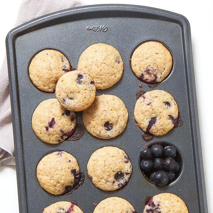 Mini muffins in a muffin tin with blueberries in a cup.