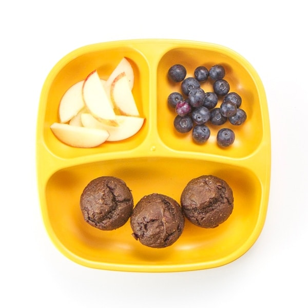 toddler plate filled with healthy muffins and fruit.