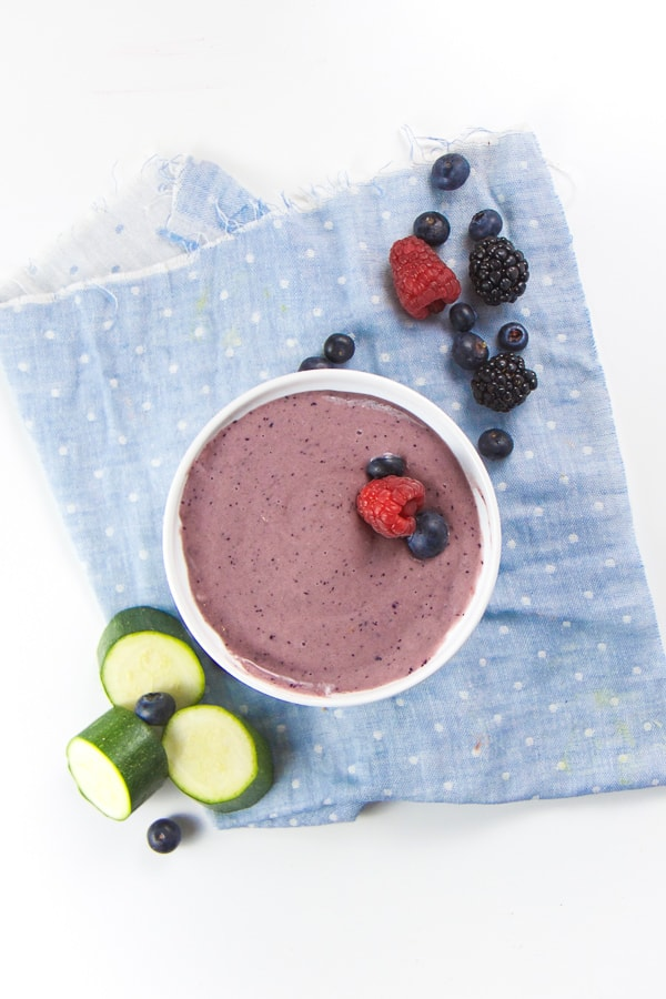 A bowl of Berry Zucchini Baby Breakfast Cereal with a blue linen napkin.