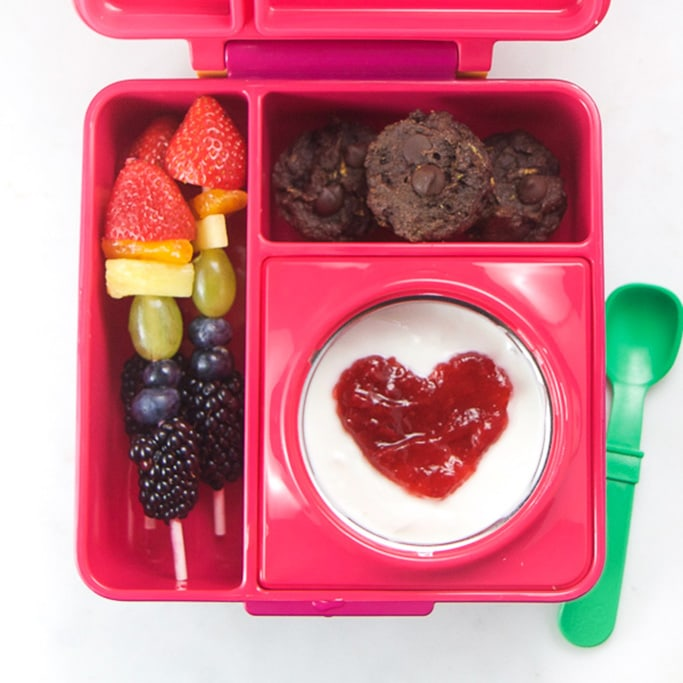 Pink school lunch box filled with healthy school lunch ideas - yogurt, rainbow fruit and chocolate muffins