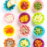 Various finger foods for baby led weaning in colorful silicone baking cups on a white background.