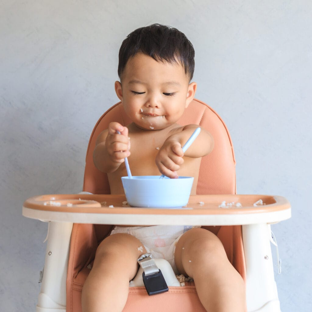 Small baby sitting in a high chair eating with two spoons.