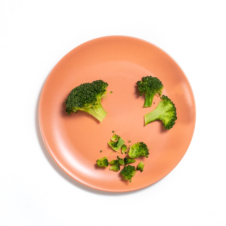 broccoli cut 3 different ways on a pink baby plate.